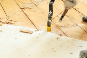 Removing subfloor with crowbar and hammer, DIY