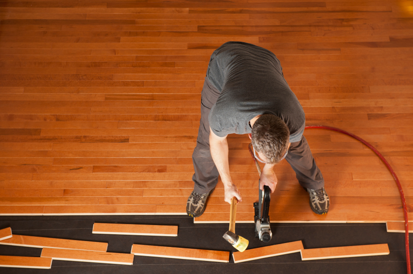 Top view of a man installing planks of hardwood floor