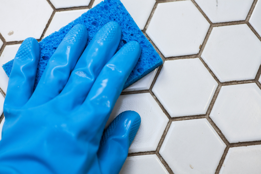 a person wearing blue gloves holds a sponge cleaning a white tile floor