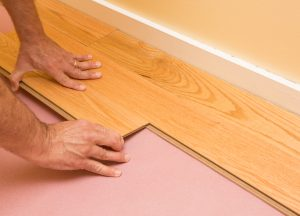 Series of shots of engineered hardwood floor being installed by a worker over pink felt paper using hand tools