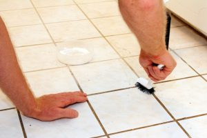 Two caucasian male hands cleaning kitchen grout of an old, dirty tile floor with environmentally friendly hydrogen peroxide, baking soda and a scrub brush..