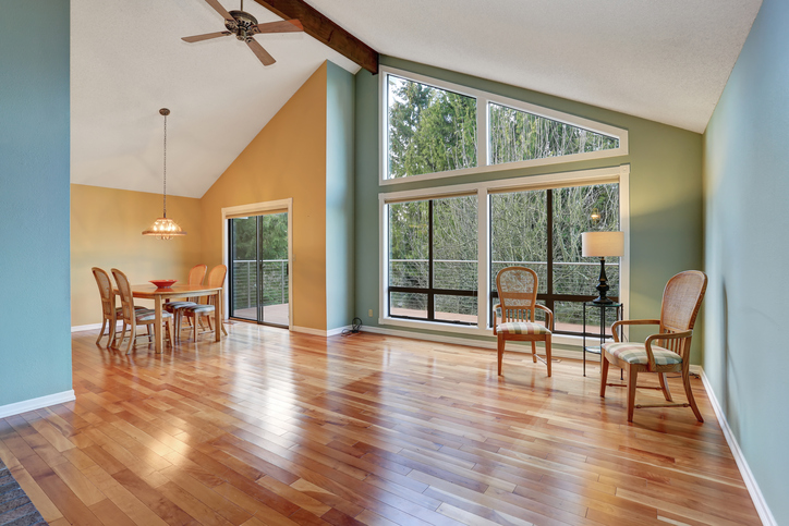 Large dinning area with hardwood floor and big windows.
