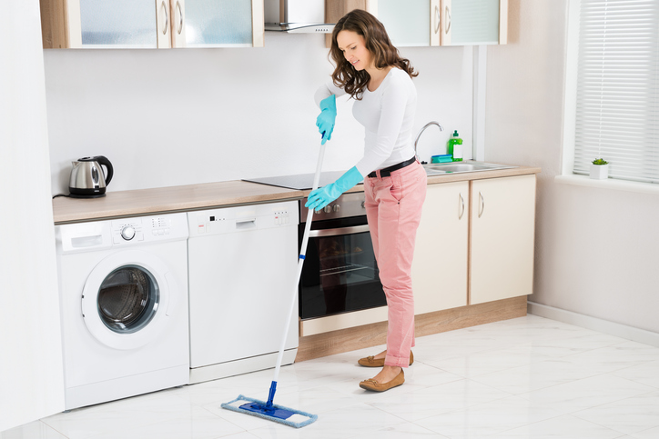 Happy Woman Cleaning Floor With Mop In Kitchen At Home