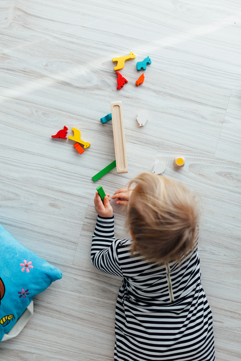 Little girl playing with wooden colorful toys
