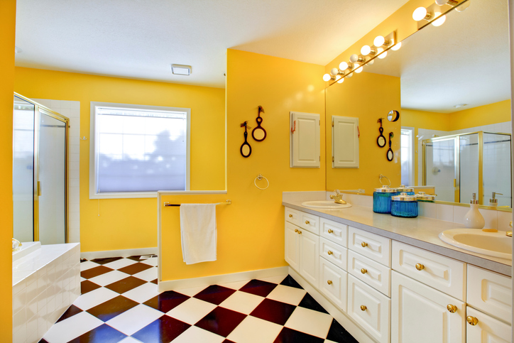 Bright yellow bathroom interior with white cabinets, tile, big mirror and glass shower