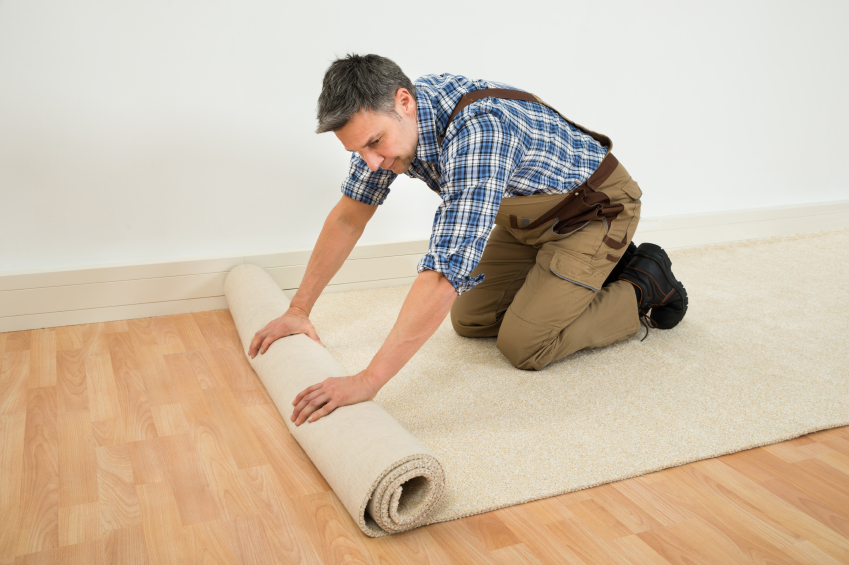 Male Worker Unrolling Carpet On Floor At Home
