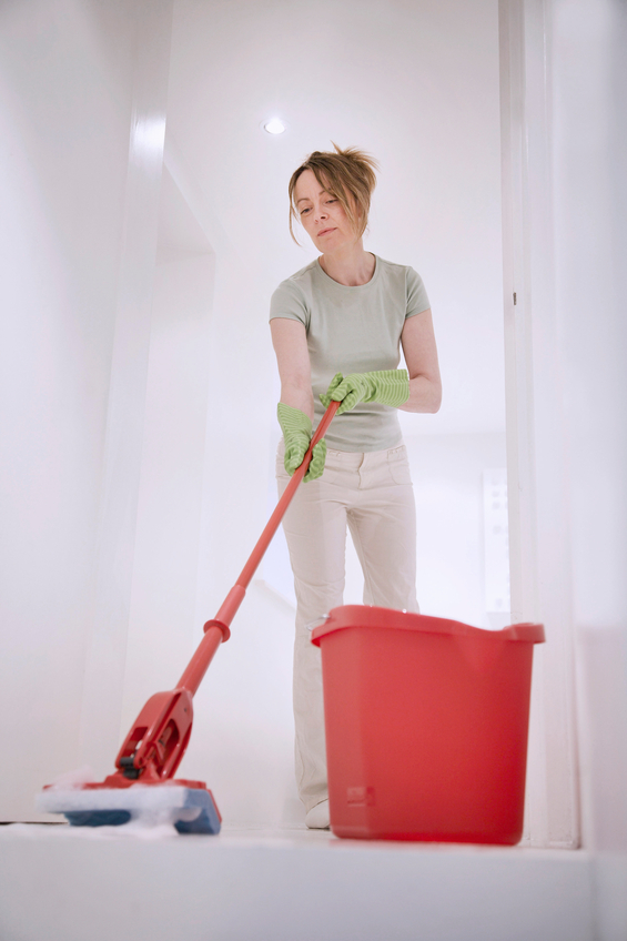 Female cleaner with mop and bucket cleans the floor of a modern hotel / office / home interior.