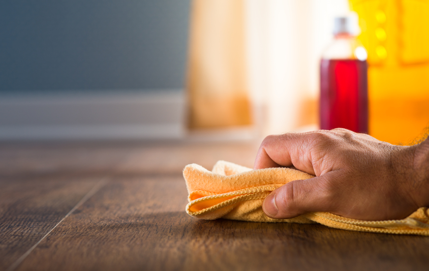 Male hand applying wood care products and cleaners on hardwood floor surface.