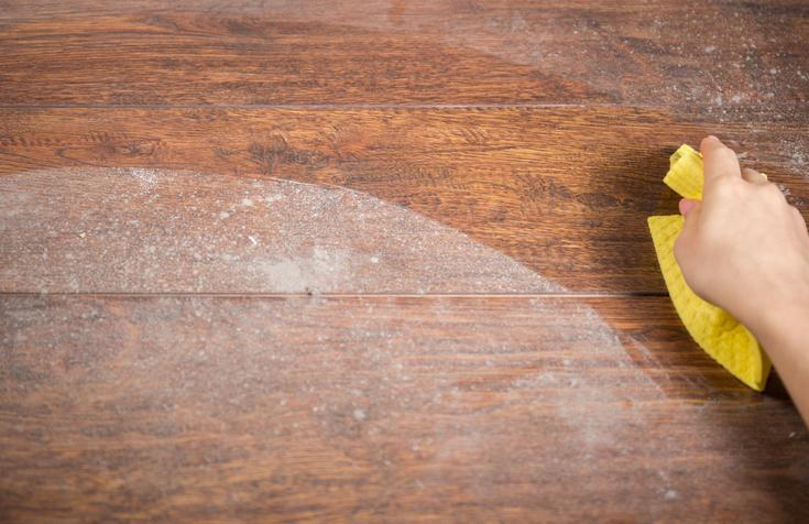 Wiping dusty wood using yellow rag