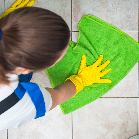 Woman in workwear cleans floor with green rag