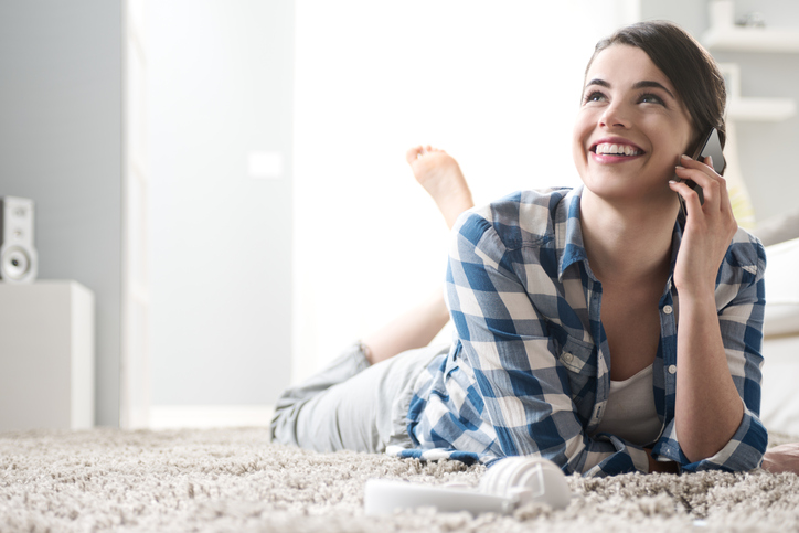 Smiling woman on the phone lying down on carpet in the living room.