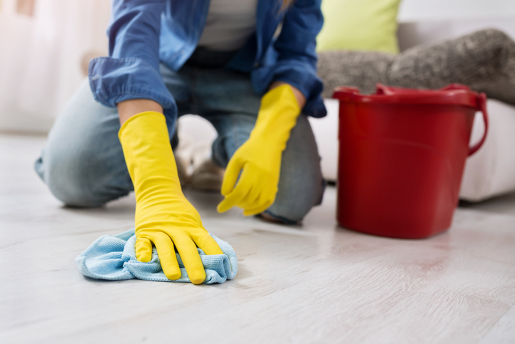 woman with gloves cleans the floor close up