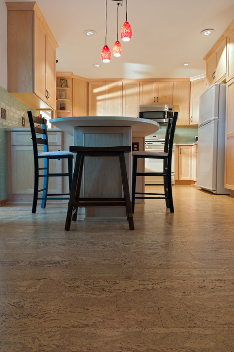Newly remodeled kitchen interior with cork floors maple cabinets and pendant lights